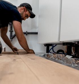 Man die een houten vloer legt