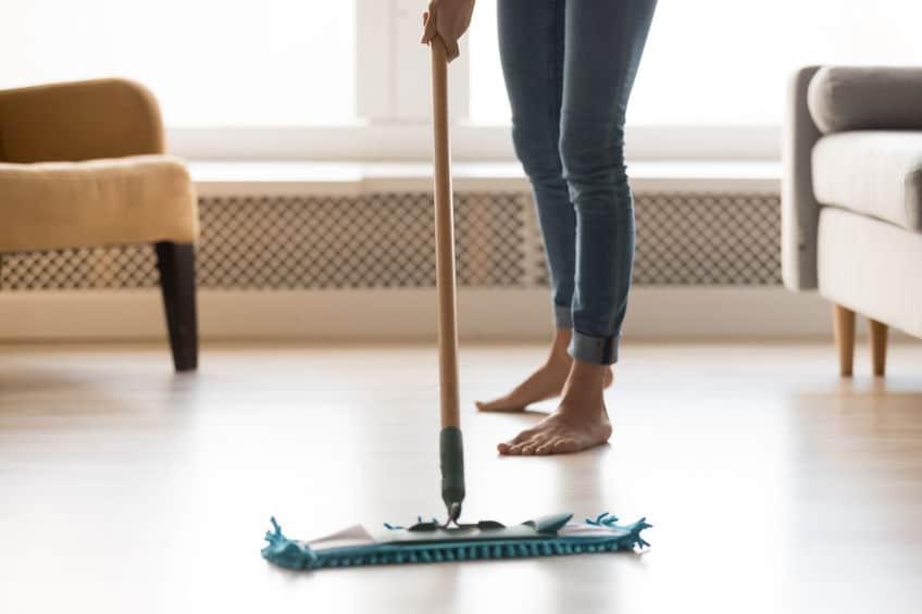 Vrouw die laminaat schoonmaakt en dweilt
